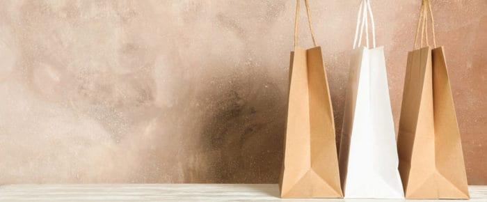 trois sacs kraft brun contre un mur couleur saumon