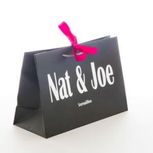 un sac papier de luxe noir avec ruban rose