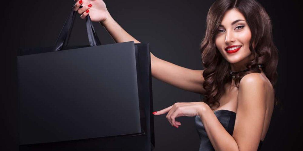 Une dame tenant des sacs papier luxe publicitaires personnalisables sur fond noir