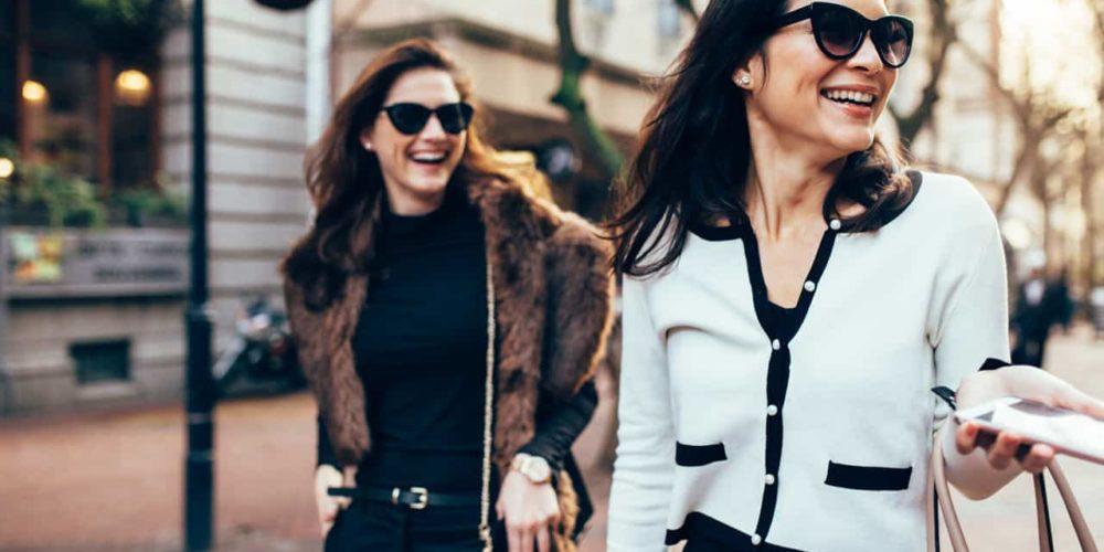 deux dames se promenant dans la rue avec des sacs publicitaires