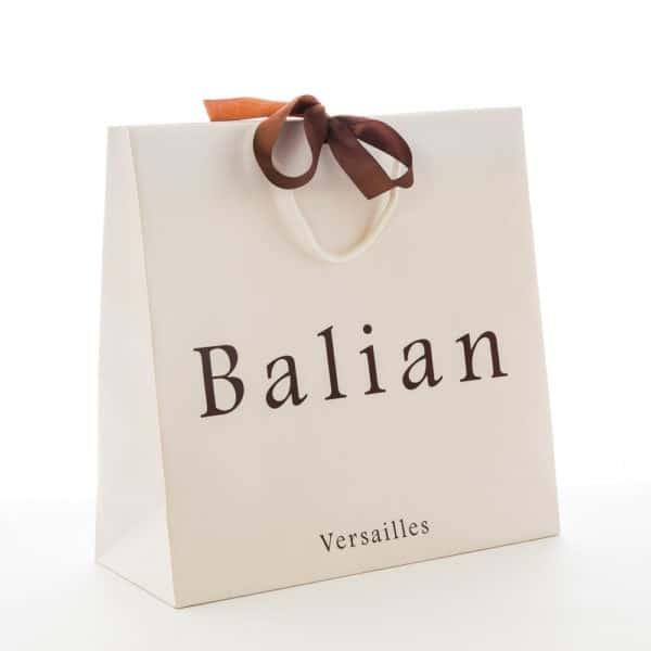 un sac papier luxe blanc avec ruban